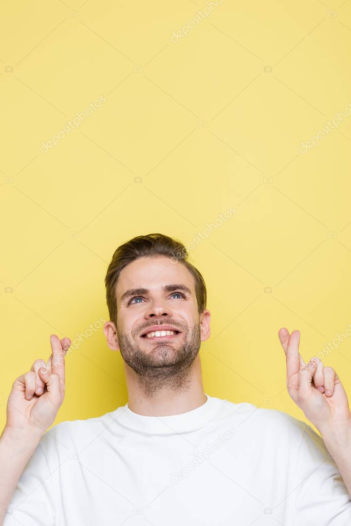 Positive man holding crossed fingers while looking up on yellow stock vector