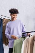 Lächelnder afrikanisch-amerikanischer Showroom-Besitzer mit Smartphone in der Nähe von Hemden auf Kleiderbügeln