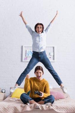 KYIV, UKRAINE - NOVEMBER 20, 2020: cheerful teenage girl holding joystick near amazed mother jumping on bed stock vector