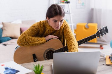 teenage girl looking at laptop while learning how to play acoustic guitar
