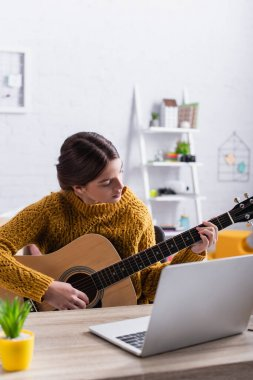 teenage girl learning how to play acoustic guitar near laptop