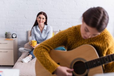 happy mother looking at teenage girl playing acoustic guitar on blurred foreground