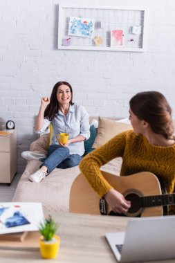 cheerful mother looking at teenage girl playing acoustic guitar on blurred foreground