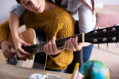 Cropped view of mother assisting teenage girl playing acoustic guitar stock vector