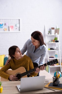 mother and teenage girl playing acoustic guitar near laptop