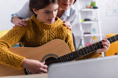 teenager biting lips while learning how to play acoustic guitar near mother on blurred background
