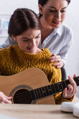 teenage girl biting lips while learning how to play acoustic guitar near mother