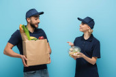 radostný kurýr ukazující na krabici s obědem poblíž arabského kolegy s jídlem v papírové tašce na modré