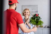 potěšená žena v blízkosti arabské dodávky muž drží kytice na rozmazané popředí