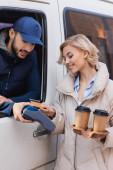 usmívající se žena s kávou jít platební příkaz s kreditní kartou v blízkosti arabského doručovatele
