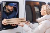 Arabské dodávky muž v kamionu dávat pizza boxy na blondýny
