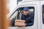 pozitivní doručovatel drží balíček při pohledu z okna auta na rozmazané popředí