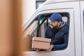 muslimský doručovatel s kartonovou krabicí při pohledu z okna auta na rozmazané popředí
