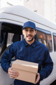 cheerful arabian postman looking at camera while holding parcel