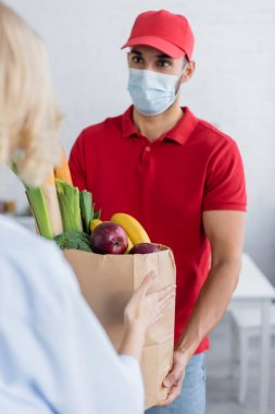 Muslim delivery man in medical mask holding fresh food in paper bag near woman on blurred foreground stock vector