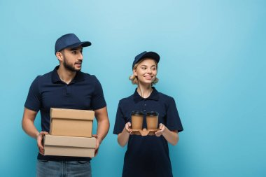 Smiling interracial couriers looking away while holding coffee to go and carton boxes isolated on blue stock vector