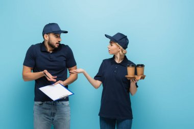 courier with takeaway drink pointing at confused arabian colleague with empty clipboard isolated on blue