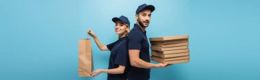 Smiling courier with paper bag standing back to back with muslim courier with pizza boxes on blue, banner stock vector