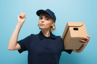 serious courier pointing up with finger while holding parcel on blue