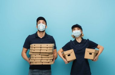 Interracial couriers in medical masks looking up while holding packages on blue stock vector