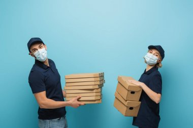 Multicultural couriers in protective masks, with pizza boxes and packages on blue stock vector