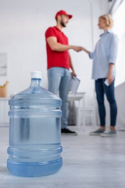 Selective focus of big bottle of potable water near muslim courier and woman shaking hands on blurred background stock vector