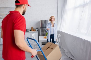 joyful woman pointing at arabian man with trolley on blurred foreground