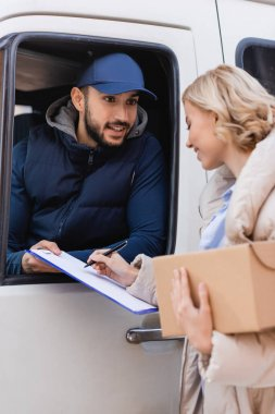 Blonde woman signing order on clipboard while holding parcel near smiling arabian postman, blurred foreground stock vector