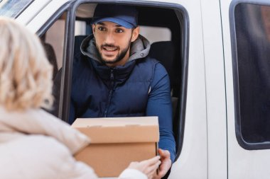 smiling muslim delivery man giving parcel to client on blurred foreground