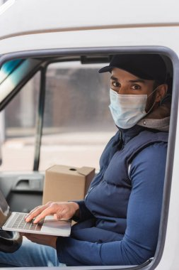 Muslim delivery man in medical mask typing on laptop in car stock vector