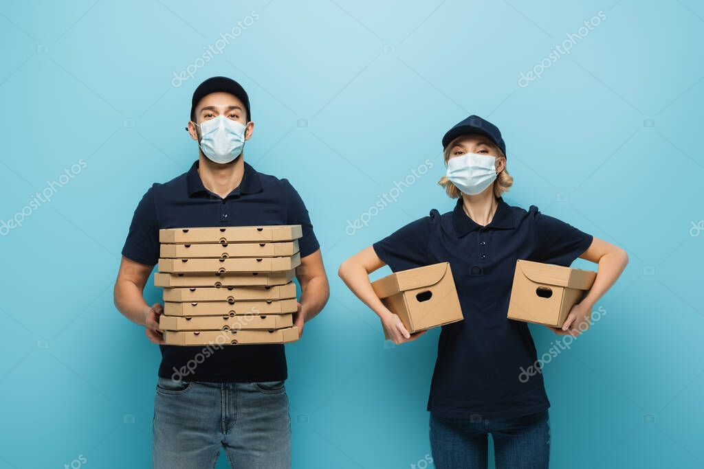 Interracial couriers in protective masks holding pizza boxes and carton packages on blue stock vector