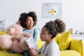 mladá africká americká žena čtení knihy na dítě sedí na gauči s medvídkem