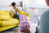 kid holding happy mothers day card near african american woman reading book on sofa, blurred background