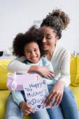 radostná africká americká žena objímající veselou dceru držící přítomné a šťastné matky den karty