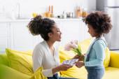 usmívající se africký americký dítě představující tulipány a šťastný matka den karta na šťastný maminka