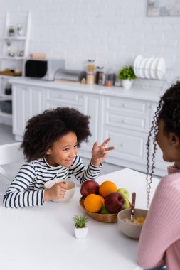 Smiling african american girl gesturing while having breakfast and talking to mother on blurred foreground stock vector
