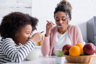 African american mother and daughter having breakfast near fruits on blurred foreground stock vector