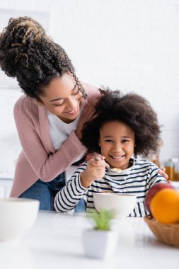 Smiling african american woman touching hair of cheerful daughter having breakfast in kitchen stock vector