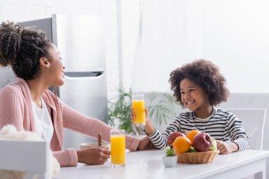 Joyful african american girl holding glass of orange juice near mother during breakfast stock vector