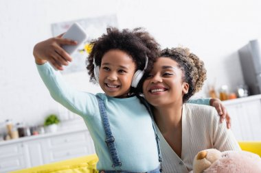 cheerful african american girl in headphones taking selfie on smartphone with happy mother