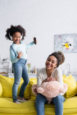 happy african american girl in headphones showing like near cheerful mother with teddy bear