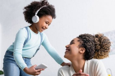 cheerful african american child in headphones holding smartphone while looking at happy mom
