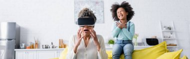 Frightened african american woman gesturing in vr headset near cheerful daughter, banner stock vector