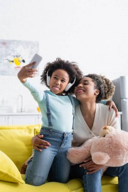 african american girl in headphones and woman with teddy bear taking selfie while sticking out tongues