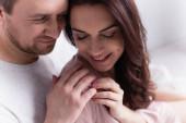 Usmívající se dospělý pár dotýkající se rukou doma