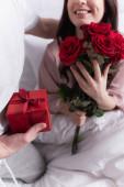 Ausgeschnittene Ansicht einer lächelnden Frau mit Rosen in der Nähe ihres Mannes mit Geschenk auf dem Bett