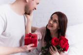 Usmívající se žena s růžemi dotýkající tvář manžela s dárečkem na posteli