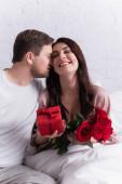 Mann küsst glückliche Frau mit Rosen und Blumen im verschwommenen Vordergrund im Schlafzimmer