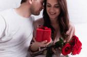Dárek a květiny v rukou šťastné ženy v blízkosti manžela doma
