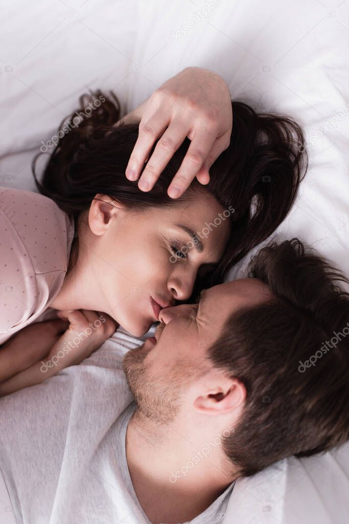 Top view of brunette woman kissing nose of smiling husband on bed stock vector